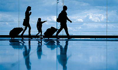 A silhouette of a family walking through an airport