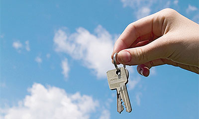 Woman holding up some keys with the sky in the background