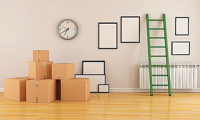 A room in a house with moving boxes laying around, and empty picture frames on the wall